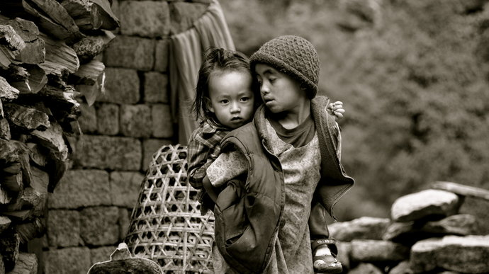 A child carries a smaller child on their back