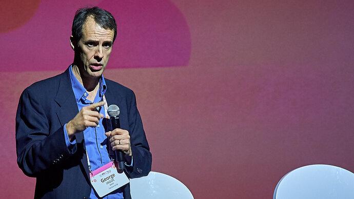Man George Jagoe) speaking on a stage