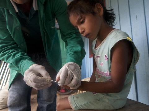 child having a finger prick blood sample taken by medical professional