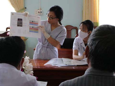 Woman conducting training session - showing materials to participants